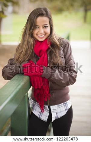 Pretty Festive Smiling Woman Portrait Wearing a Red Scarf and Mittens Outside. - stock photo