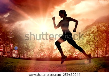 Pretty fit blonde jogging against sun shining over park - stock photo