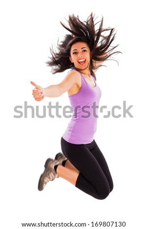 Pretty fit girl showing like sign while jumping high - studio shot. - stock photo
