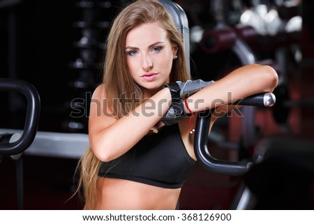 Pretty fit girl with long brown straight hair and nude make up wearing black short top and gloves sitting in gym.