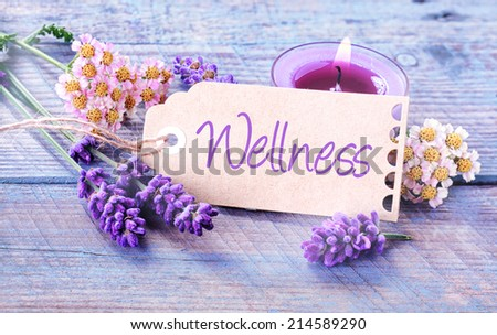 Pretty floral Wellness background with fresh scented lavender and dainty inflorescences around a label with the script - Wellness - leaning against a burning purple aromatherapy candle in a spa - stock photo