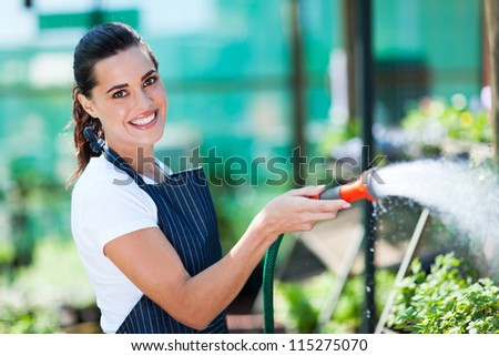 pretty florist watering flowers in greenhouse - stock photo