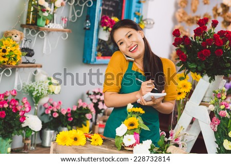 Pretty flower girl talking on the phone - stock photo