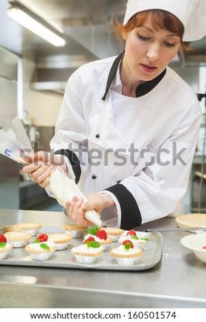 Pretty focused head chef preparing dessert in professional kitchen - stock photo