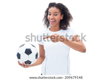 Pretty football fan in white holding ball and pointing to it on white background - stock photo
