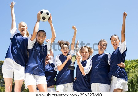 Pretty football players celebrating their win on a sunny day - stock photo