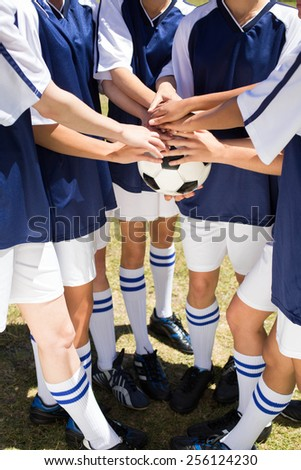 Pretty football players putting hands together on a sunny day