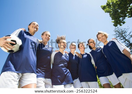 Pretty football players smiling at camera on a sunny day - stock photo
