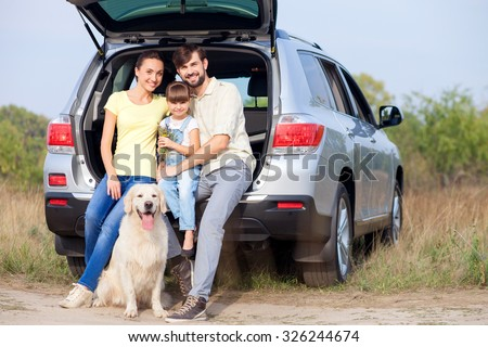 Pretty friendly family is making trip in the nature. They are sitting on car boot near dog and smiling. The man and woman are embracing their daughter. They are looking at camera with happiness - stock photo