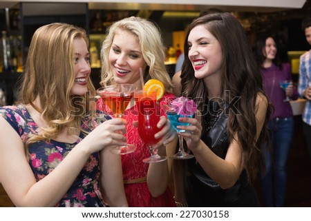 Pretty friends drinking a cocktail at the bar - stock photo