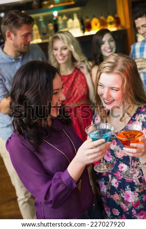 Pretty friends drinking cocktails together at the bar - stock photo