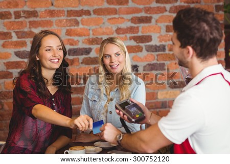 Pretty friends handing a credit card at the coffee shop