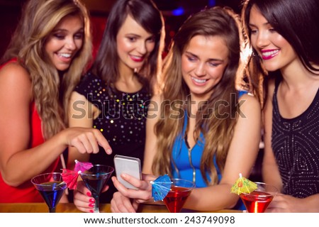 Pretty friends looking at smartphone together at the nightclub - stock photo