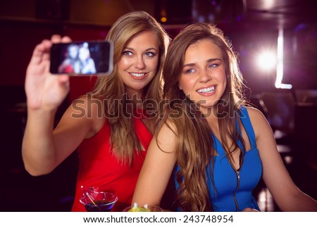 Pretty friends taking a selfie at the nightclub