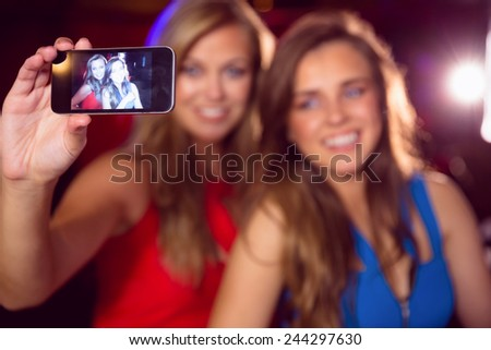 Pretty friends taking a selfie at the nightclub - stock photo