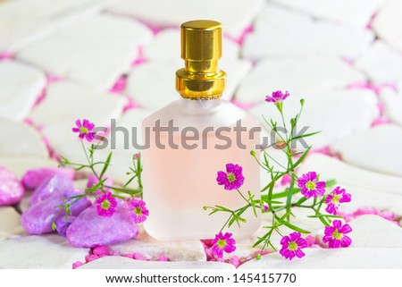 Pretty frosted bottle of perfume or natural floral essence surrounded by sprigs of delicate fresh purple flowers with copy space - stock photo
