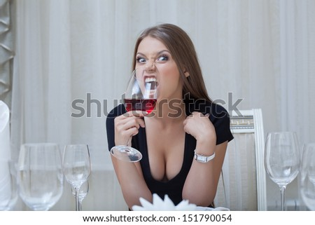Pretty funny girl biting glass of wine, close-up - stock photo