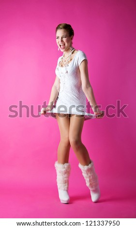 Pretty funny laughing and shouting bride girl wearing white wedding dress, white high heels shoes, pearls and beads, dancing and having fun in studio against pink background - stock photo