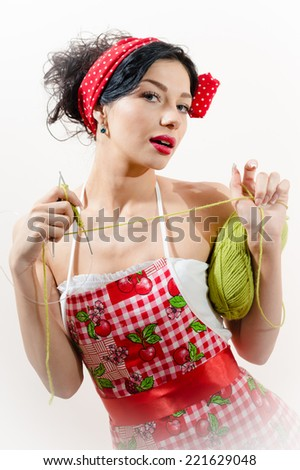 Pretty funny young brunette pinup woman with green knitting tread looking at camera posing