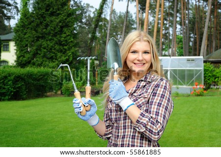 Pretty gardener woman with gardening tools outdoors. greenhouse on the background - stock photo