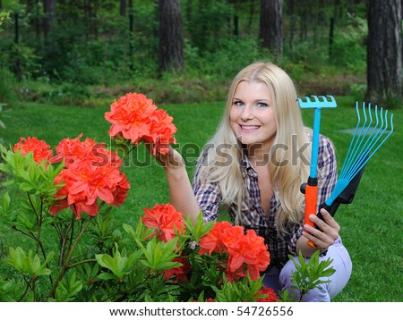 Pretty gardener woman with red flower bush and gardening tools outdoors