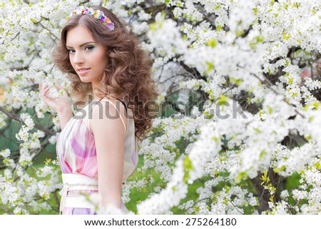 Pretty gentle young elegant beautiful girl with lush hair with a rim of brightly colored flowers in a garden near a flowering tree warm spring morning - stock photo