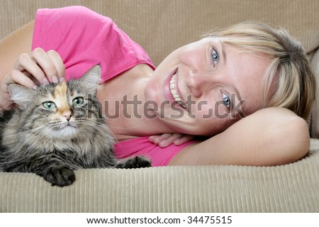 Pretty girl and cute cat on the sofa - stock photo