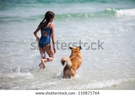 pretty girl and her dog running on the water at the beach - stock photo