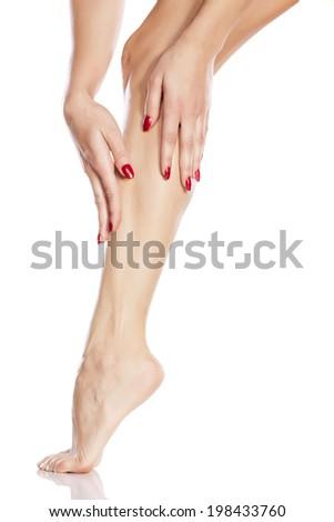 pretty girl apply cosmetics on her leg - stock photo
