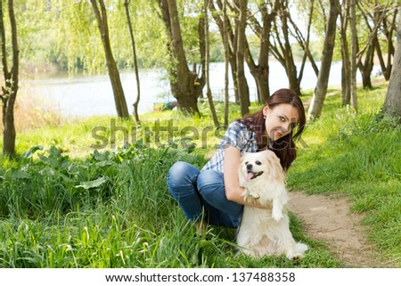 Pretty girl bending down and posing her cute little dog for the camera alongside a lush green rural path through woodland - stock photo