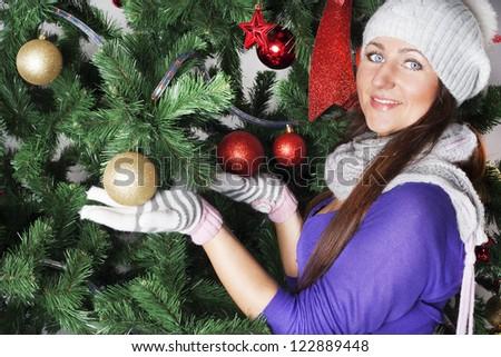 Pretty girl beside green Christmas Tree - stock photo