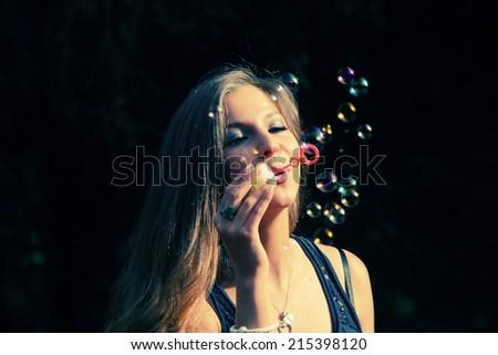 pretty girl blowing bubbles - stock photo