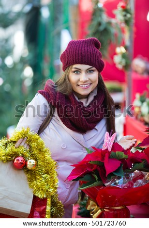 Pretty girl buying floral compositions at the Christmas fair