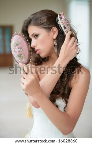 pretty girl combs luxurious dark hairs, does hairstyle - stock photo