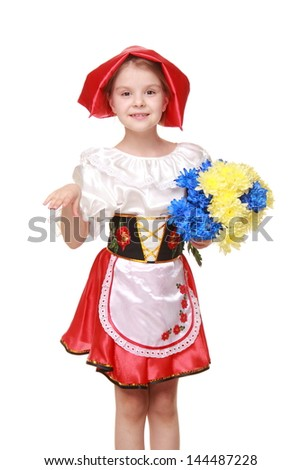 Pretty girl dressed as Little Red Riding Hood is holding a beautiful bouquet of blue and yellow chrysanthemums on Holiday
