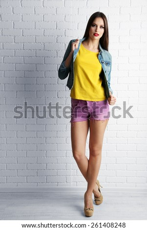 Pretty girl dressed in casual style posing on white brick wall background - stock photo