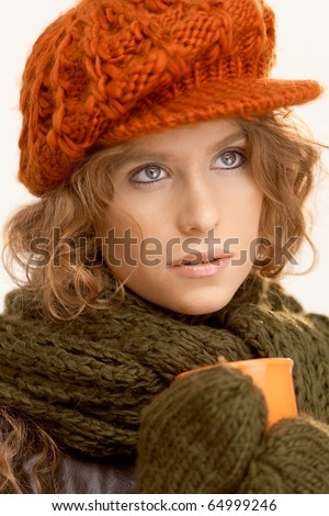 Pretty girl dressed up warm, drinking coffee, freezing, looking away.? - stock photo