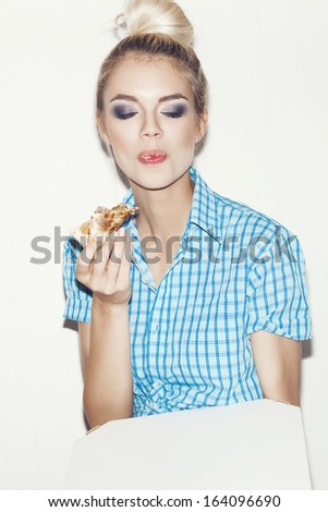 Pretty girl eating a piece of pizza. Indoors, lifestyle. - stock photo