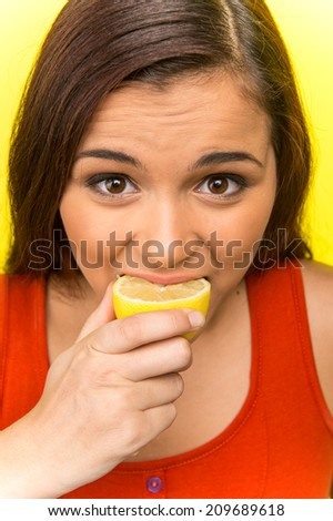 pretty girl eating fresh lemon. beautiful girl isolated on yellow background