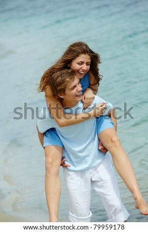 Pretty girl embracing handsome boyfriend while both laughing - stock photo