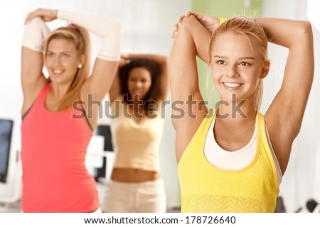 Pretty girl exercising in group, smiling, stretching. - stock photo