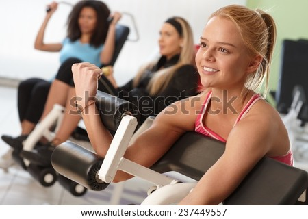 Pretty girl exercising on weight machine at the gym.