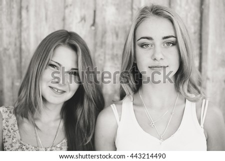 Pretty girl friends having fun. Both looking at camera and smiling on wooden background - stock photo