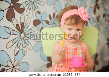 pretty girl giving yellow plastic spoon - stock photo