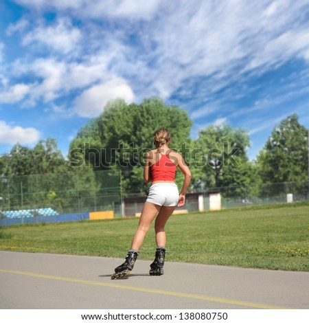 Pretty girl goes on roller skates on a beautiful sunny day