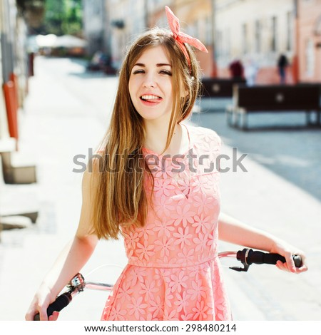 Pretty girl having fun and showing tongue, holding a bicycle handlebar in a sunny day on the street of the old town. Young woman wearing pink head wrap and pink dress with a pattern of flowers. - stock photo