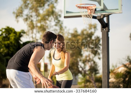 Pretty girl having some fun on her first date playing basketball outdoors - stock photo