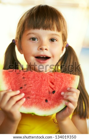 Pretty girl holding a piece of watermelon