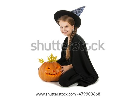 Pretty girl holding a pumpkin. Halloween. The girl smiles. Joy, emotion, holiday.