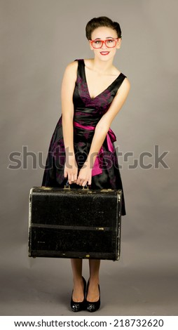 Pretty girl holding an old suitcase while wearing big red glasses in front of a grey background - stock photo
